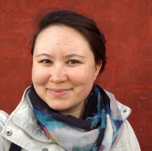 Headshot of Celeste standing in front of red wall wearing khaki coat and multicolored scarf